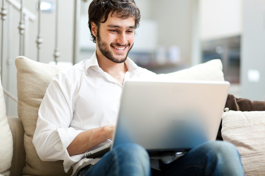 Man using his laptop while sitting on the couch