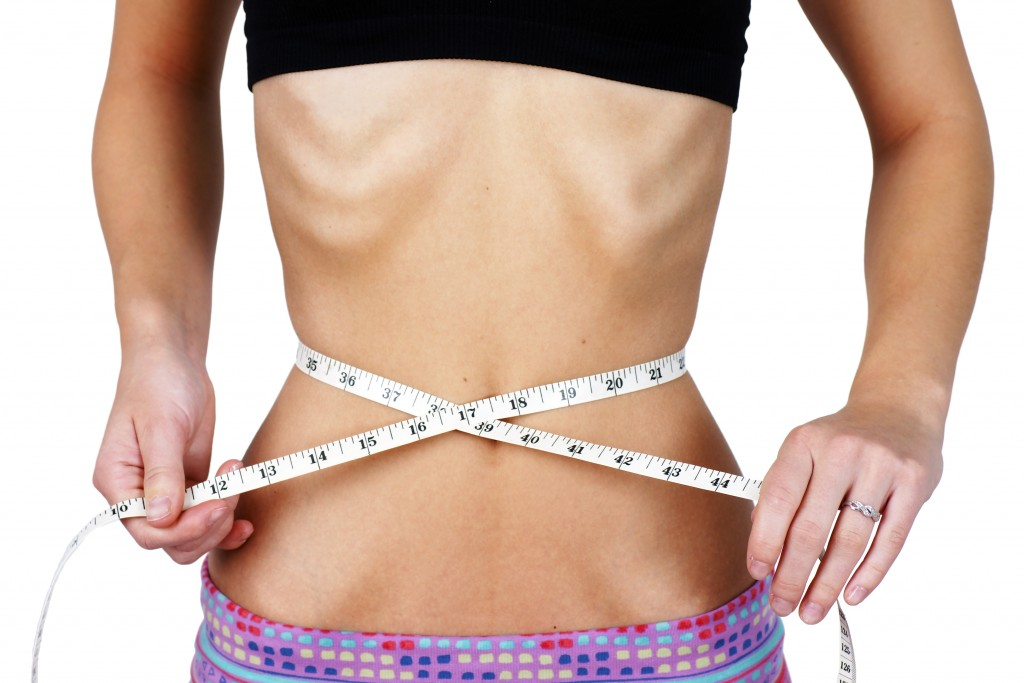girl with anorexia measuring her waist