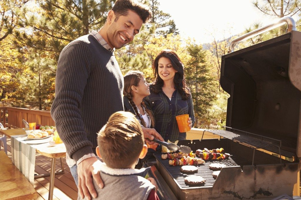 Whole family grilling barbecue