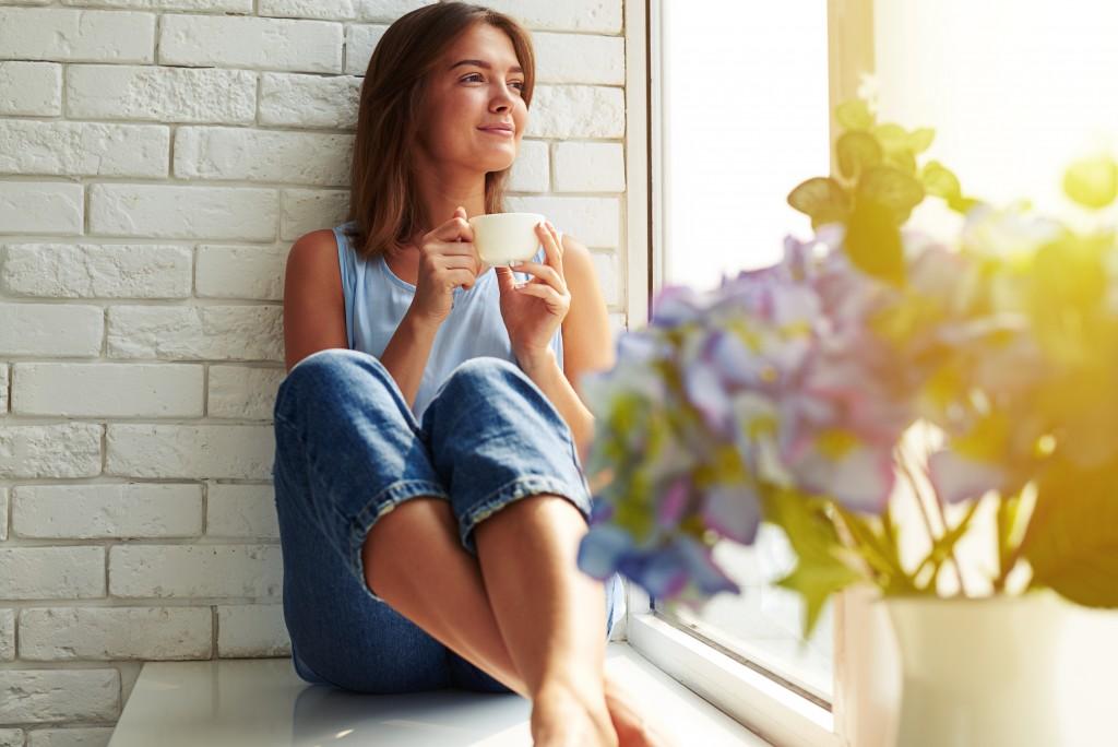 young woman drinking coffee beside her window pane