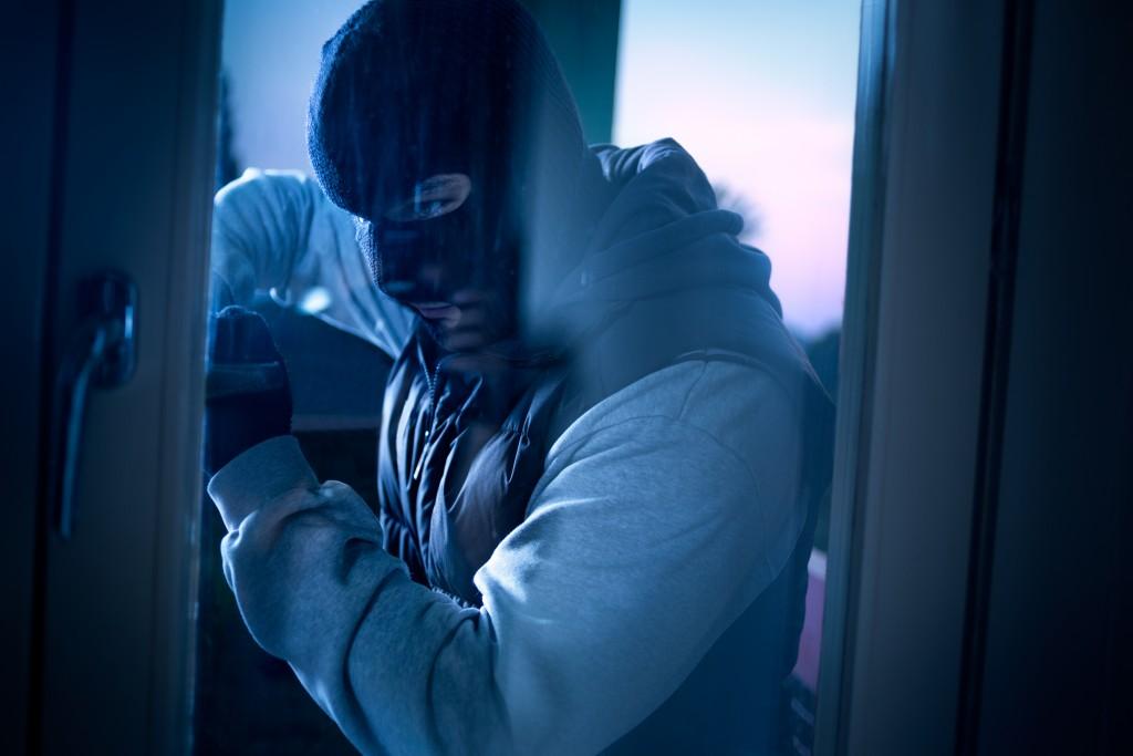burglar with crowbar breaking the door to enter the house